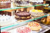 stock photo of french pastry  - Pastry shop glass display with selection of cream or fruit cake - JPG