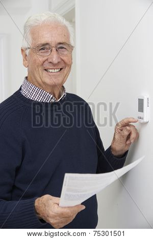 Smiling Senior Man With Bill Adjusting Central Heating Thermostat