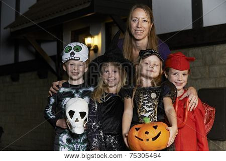 Halloween Party With Children Trick Or Treating In Costume With Mother