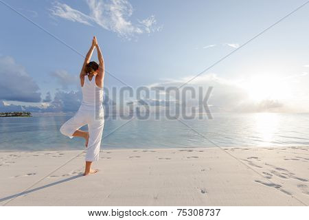 Caucasian woman practicing yoga at seashore, ocean