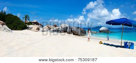 Family on picture perfect beach with blue umbrella, white sand, turquoise ocean water and blue sky at tropical island in Caribbean