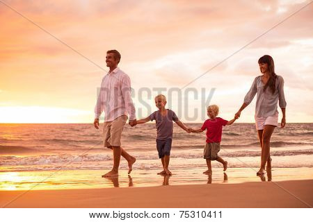 Happy Young Family of Four on the Beach at Sunset