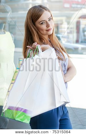 Girl With Shopping Bags Stands Near The Storefront