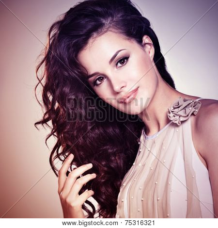 Beautiful young woman with long brown hair. Pretty model poses at studio. Concept image is in tinting colorize style