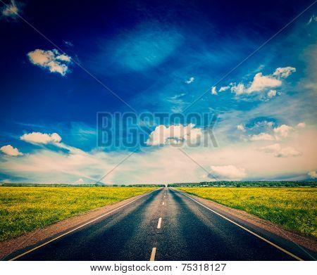 Vintage retro effect filtered hipster style image of travel concept background - road in blooming spring meadow