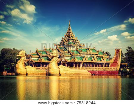 Vintage retro effect filtered hipster style image of Yangon icon landmark and tourist attraction:  Karaweik - replica of a Burmese royal barge at Kandawgyi Lake, Yangon, Myanmar (Burma)