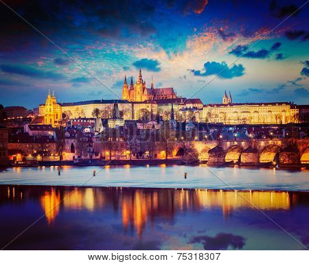 Vintage retro hipster style travel image of Prague Europe concept background - view of Charles Bridge and Prague Castle in twilight. Prague, Czech Republic
