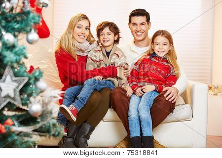 Happy family and children celebrating christmas with a christmas tree