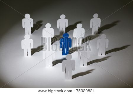 Close up of group of standing paper-men. Lots of similar copies of a paper man, but a blue one stands out among them. Concept of teamwork and leadership