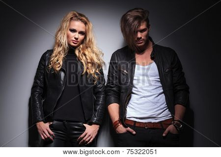 Young fashion couple looking at the camera while leaning on a grey wall, both holding hands in pockets.