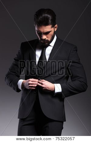 Elegant business man closing his jacket while looking down, on grey background.