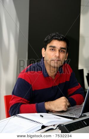 Young Indian Student Working On His Laptop In The University.