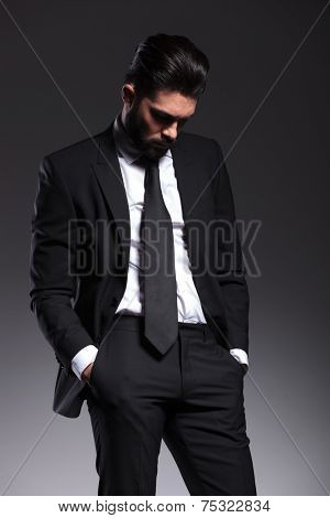 Picture of a elegant businss man looking down, holding his hands in pockets.
