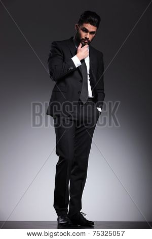 Elegant business man looking at the camera while petting his beard, full body image.