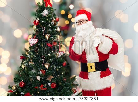 christmas, holidays and people concept - man in costume of santa claus with bag and christmas tree making hush gesture over lights background