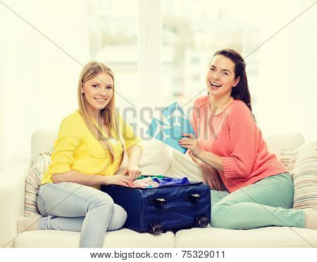 travel, vacation and friendship concept - two smiling teenage girls with plane tickets and packed suitcase