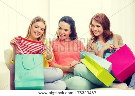 shopping and lifestyle concept - three smiling teenage girls with many shopping bags at home