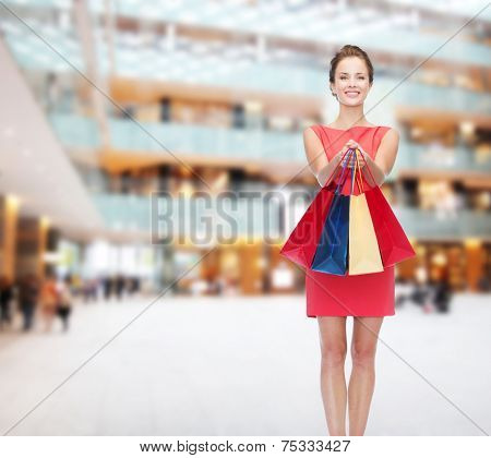 sale, christmas and holidays concept - smiling elegant woman in red dress with bags over shopping center background