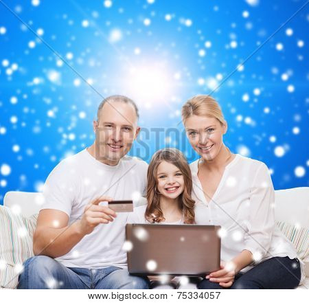 family, christmas holidays, shopping, technology and people concept - happy family with laptop computer and credit card over blue snowy background