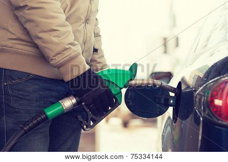 vehicle and fuel concept - close up of male refilling car fuel tank