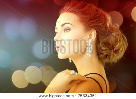 jewelry, luxury, vip, nightlife, party concept - beautiful woman in evening dress wearing diamond earrings
