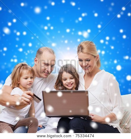 family, christmas holidays, shopping, technology and people - happy family with laptop computer and credit card over blue snowy background