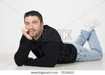 Happy Man Lying On Wooden Floor