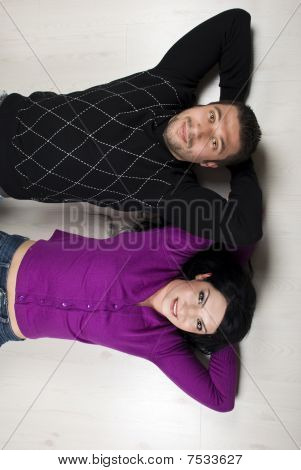 Happy Couple Lying On Floor In Their New Home
