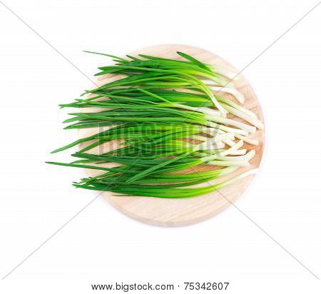 Spring onion on wooden platter.