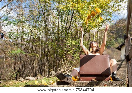 Girl Plays With Leaves In The Autumn Season