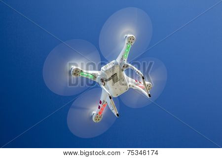 FORT COLLINS, CO, USA, November 4, 2014:  Airborne radio controlled Phantom quadcopter drone flying  - a view from the ground against blue sky.