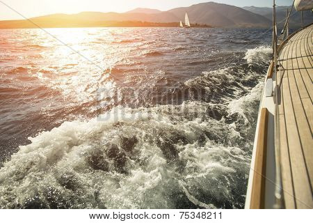 Yacht, sea overboard, sailing regatta during sunset.