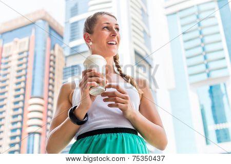 Young woman drinking coffee in metropolitan city Dubai