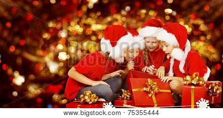 Christmas Kids Opening Present Gift Box, Happy Children In Santa Hat, Smiling Boys And Girls In Red