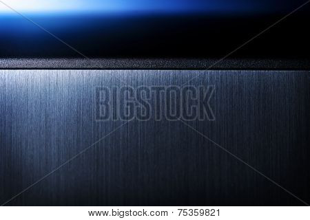 Sharp edged brushed metal and blue light background.?Shallow depth of field.
