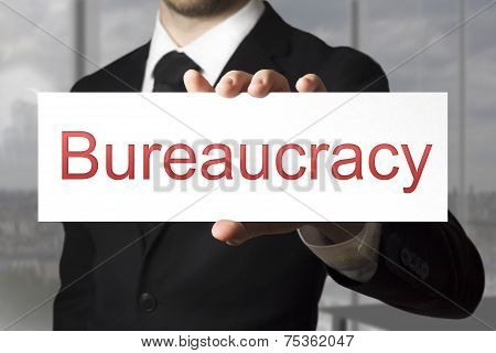 Businessman Holding Sign Bureaucracy