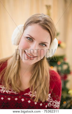Portrait of a smiling blonde wearing earmuffs at home in the living room