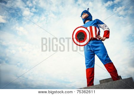 Boy dressed as Captain America on the sky background