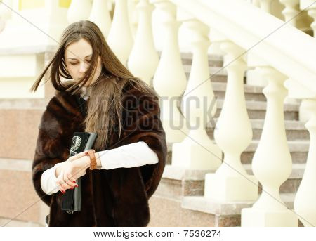 Mulher olha para seu relógio por balaustrada