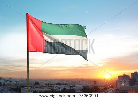 A big flag of UAE flying high on the city of Sharjah, UAE. A National Day celebration on 2nd December.