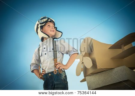 Little boy with a cardboard airplane