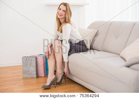 Smiling woman sitting on couch taking off her shoes at home in the living room