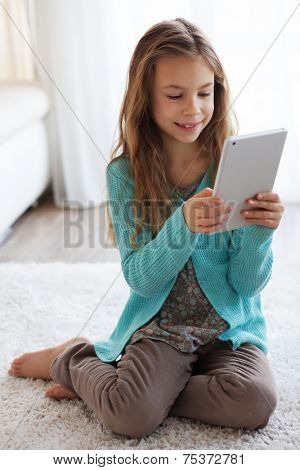 Child playing on ipad tablet pc sitting on a carpet at home