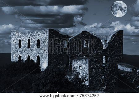 derelict castle ruin with a rising full moon, sweden