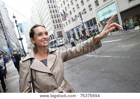 Businesswoman hailing for a taxi cab in NYC