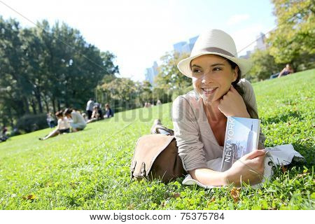 Cheerful woman in Central Park reading New York city guide