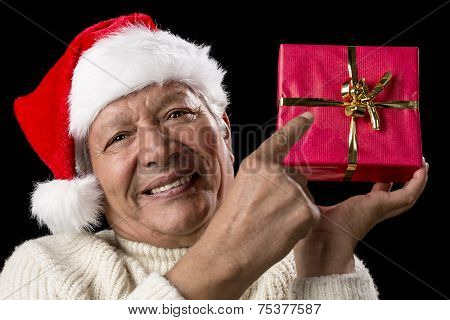 Male Senior Pointing At Red Wrapped Christmas Gift