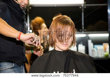 MOSCOW - OCTOBER 24: Hairstylist performs hair cut at the international exhibition of professional cosmetics and beauty salon equipment INTERCHARM on October 24, 2014 in Moscow