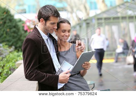 Couple of tourists in Bryant Park using tablet and city guide