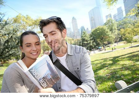 Couple of tourists looking at traveler's guide in Central Park